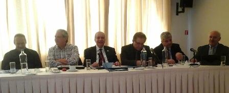 Το πάνελ των ομιλητών, στην οποία απεικονίζονται από αριστερά προς τα δεξιά οι κ.κ.:      Ι. Μπασκόζος, Α' Αντιπρόεδρος ΠΙΣ,  Δ. Βαρνάβας, Μέλος ΔΣ ΠΙΣ,    Μ. Βλασταράκος, Πρόεδρος ΠΙΣ,        Κ. Αλεξανδρόπουλος, Γεν. Γραμματέας ΠΙΣ,       Γ. Ροκαδάκης, Β' Αντιπρόεδρος ΠΙΣ,        Β. Παναγιωτίδης, Μέλος ΔΣ ΠΙΣ.